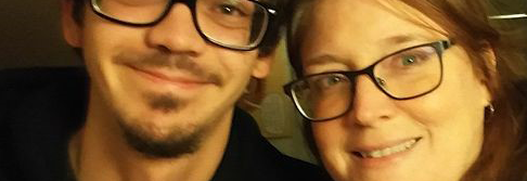 Parent and adult child smiling to the camera.