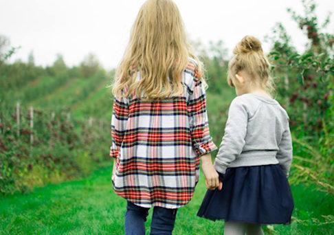 two little girls walking hand in hand in a field